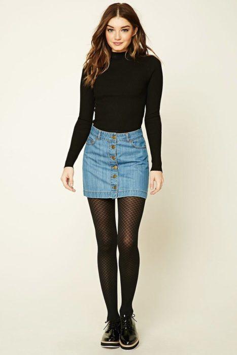 Chica usando blusa de manga larga y falda denim, con mallas y zapatos negros