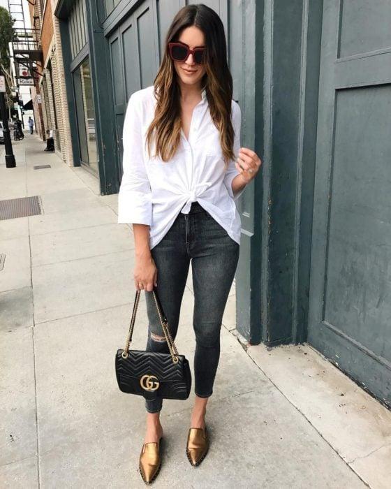 Chica usando jeans negros y camisa blanca, con zapatos dorados