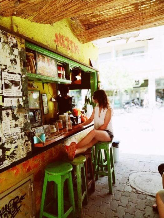 Mujer sentada en la barra de un bar