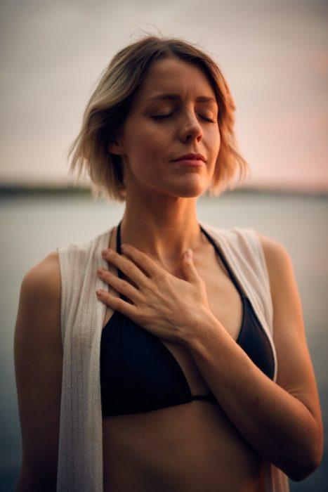 Mujer respirando y con una mano en el pecho