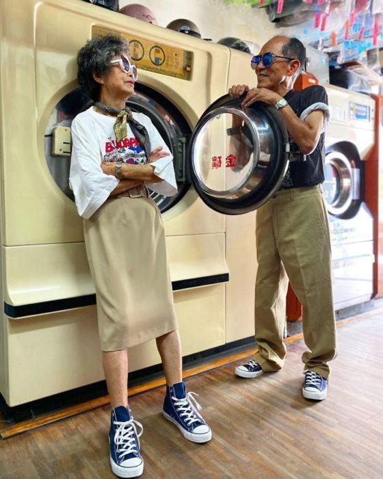 Pareja de abuelitos llevando conjuntos a juego en color beige dentro de una lavandería