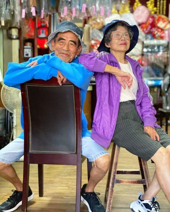 Pareja de abuelitos sentados en bancos de madera llevando sombreros estilo pescador a juego