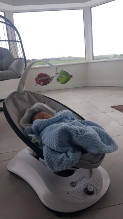 Bebé acostado en portabebés con frazada azul