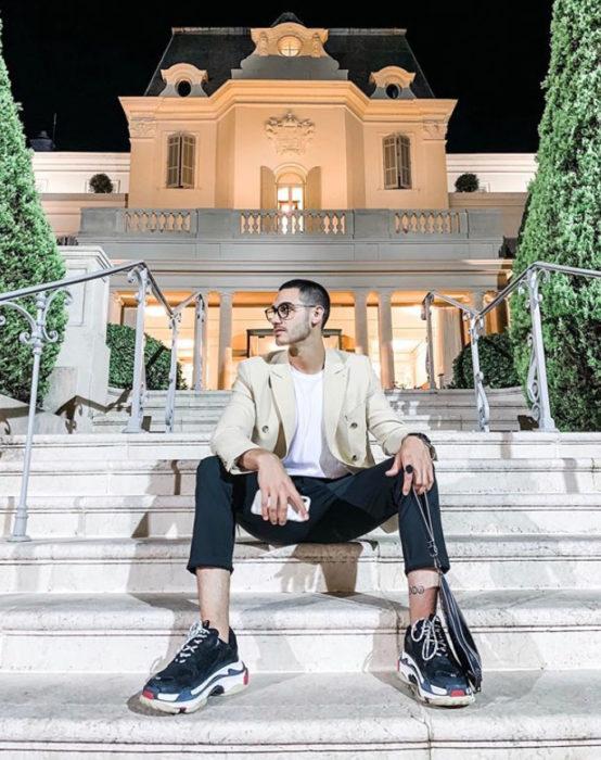 Alejandro Speitzer posando para fotografía, sentado en las escaleras usando jeans, playera blanca y tenis