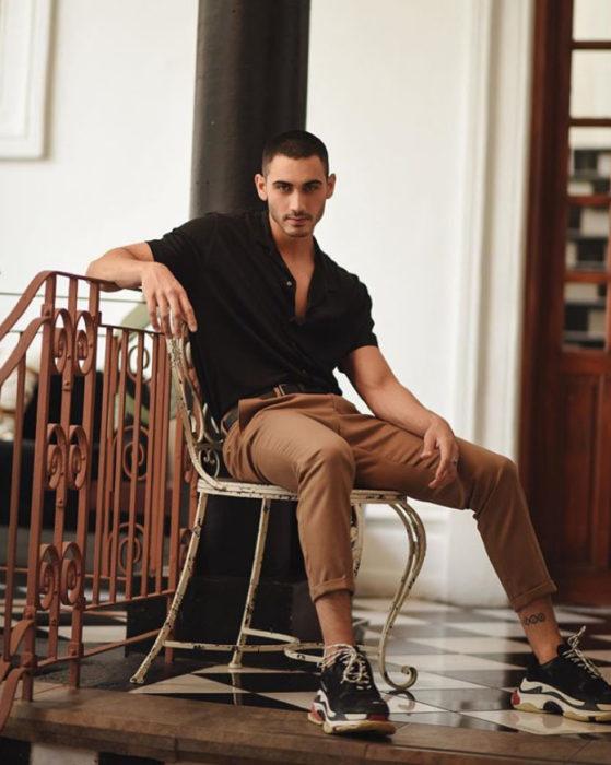 Alejandro Speitzer posando para fotografía, sentado en una silla, usando jogger cakis y camisa negra con tennis