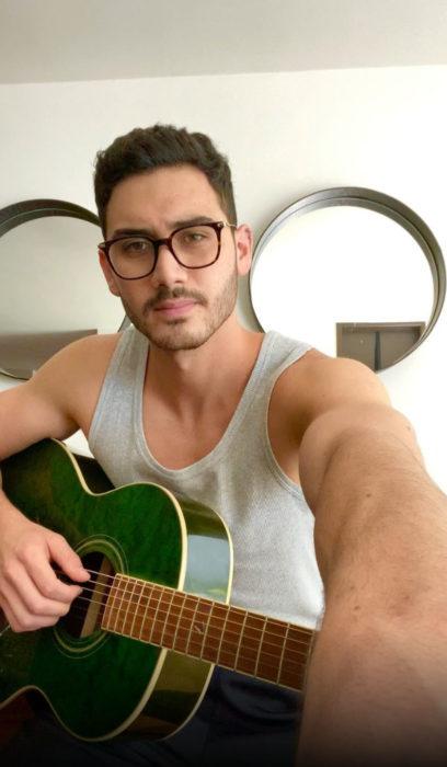 Alejandro Speitzer posando para fotografía, mientras toca la guitarra