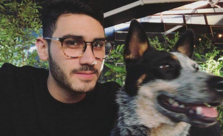Alejandro Speitzer posando para fotografía, al lado de su perro y usando un suéter negro