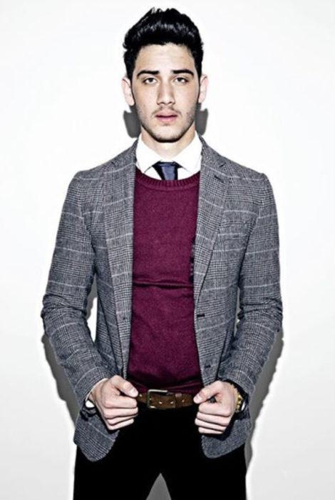 Alejandro Speitzer posando para fotografía, usando suéter color vino, y saco gris