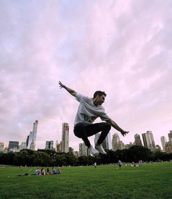Alejandro Speitzer posando para fotografía, mientras salta en un parque