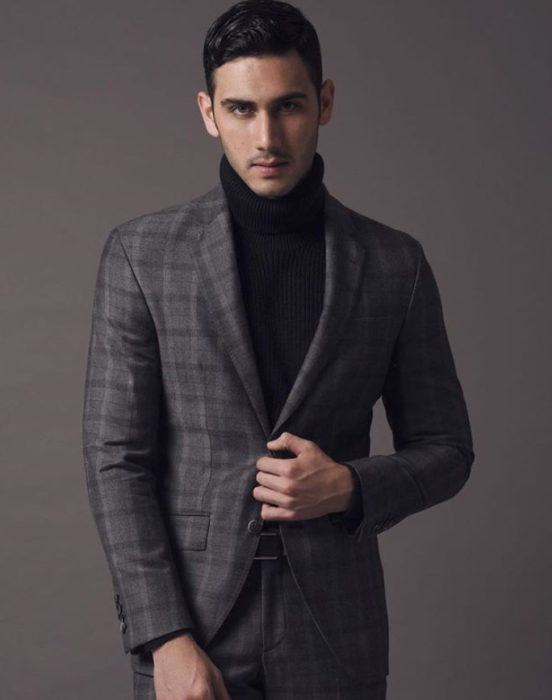Alejandro Speitzer posando para fotografía, usando suéter negro y saco gris