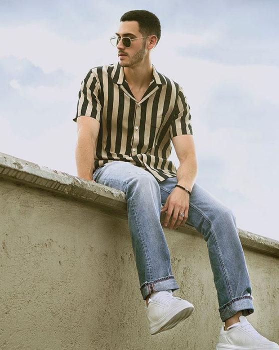 Alejandro Speitzer posando para fotografía, sentado en una barda, usando jeans y camisa de rayas