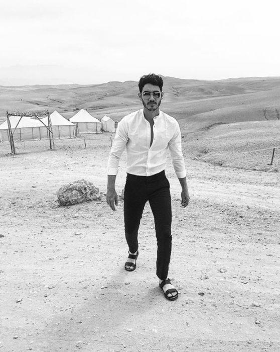 Alejandro Speitzer posando para fotografía, jeans negros, camisa blanca y sandalias negras