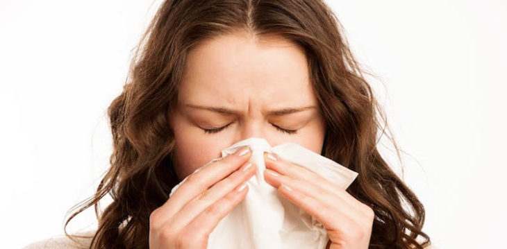 Chica alérgica estornudando con un pañuelo