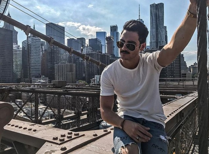 Alejandro Speitzer posando para fotografía, sentado en un punto, usando jeans, gafas de sol y playera blanca