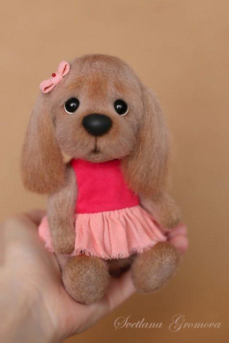 Peluche creado por la artista Svetlana Gromova, perrito café con vestido rosa