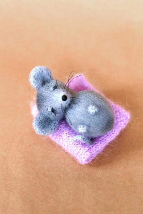 Peluche creado por la artista Svetlana Gromova, ratón miniatura de color gris recostado en una sábana rosa