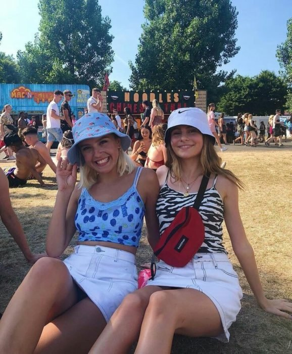 Friends with the same outfits of a tank top, white skirt and hat