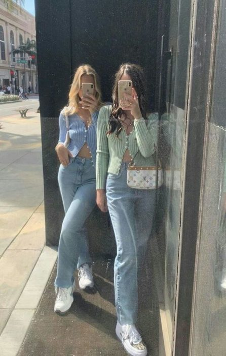 Best friends with matching outfits in pastel sweater and jeans