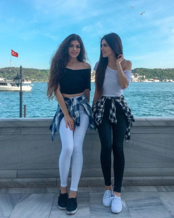 Best friends with the same outfits in black pants and white blouse