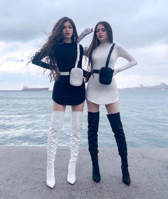 Best friends with equal outfits in black and white dresses with long boots