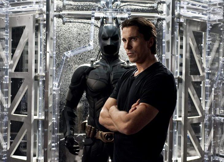Bruce Wayne de brazos cruzados y detrás el traje de Batman