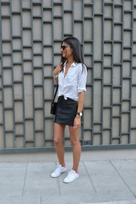 Girl wearing black vini leather mini skirt and white knotted shirts