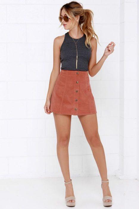 Chica usando mini falda color durazno con blusa negra sin mangas deslavada