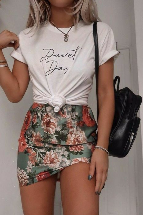 Girl wearing flowery mini skirt with white knotted blouse