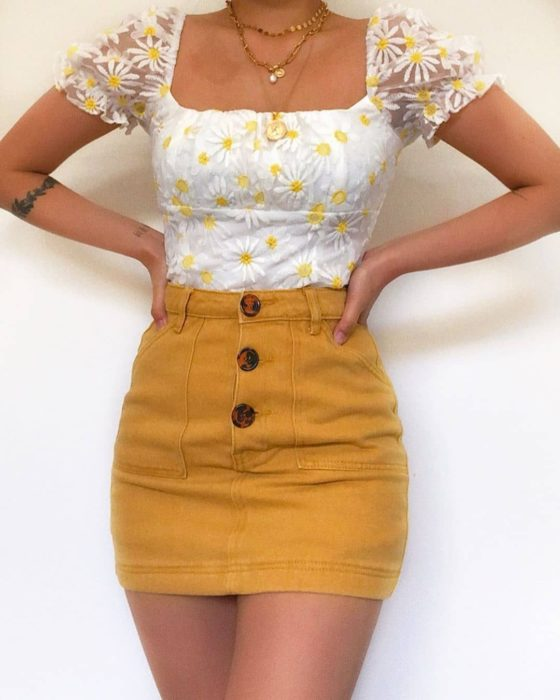 Girl wearing mustard-colored mini skirt and blana blouse with sunflower details