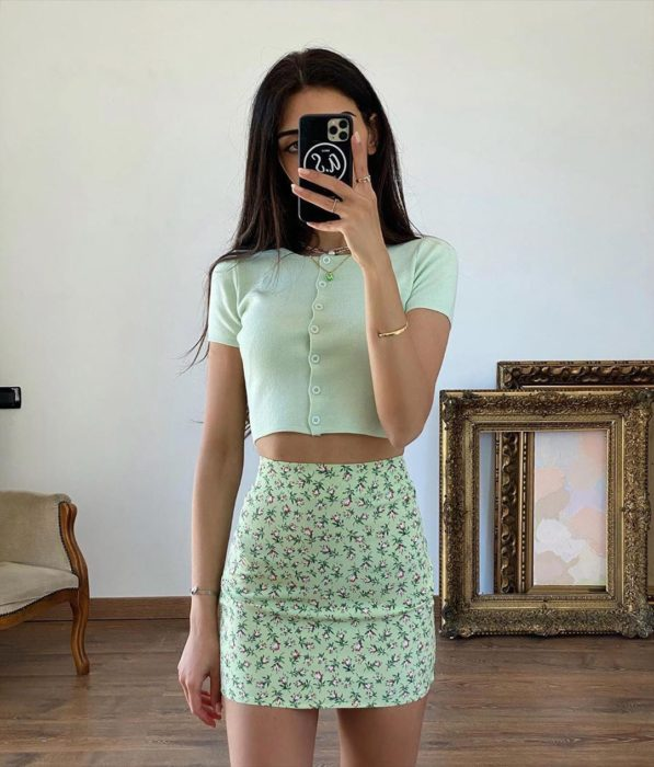 Girl wearing mint mini skirt with flowers and blouse of the same color with buttons on the front