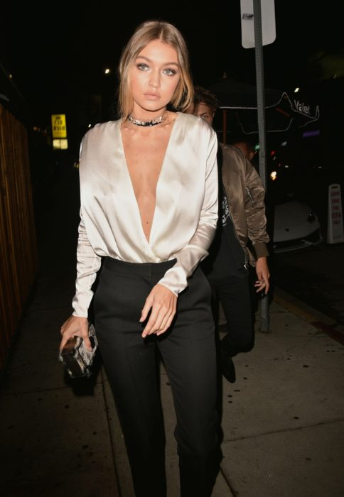 Bella Hadid wearing black pants with a champagne colored blouse