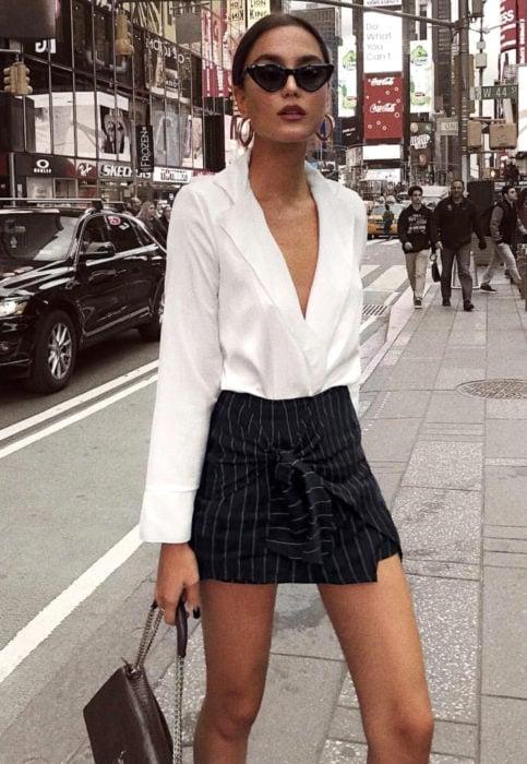 Chica usando una blusa de color blanca acompañada de un falda de rayas