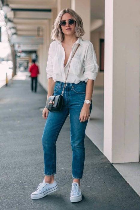 Chica usando una blusa blanca con escote, jeans y tenis