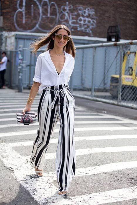 Chica usando una blusa de color blanco con pantalón de rayas y bolso negro