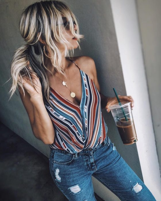 Chica usando una blusa a rayas con un pantalón de mezclilla