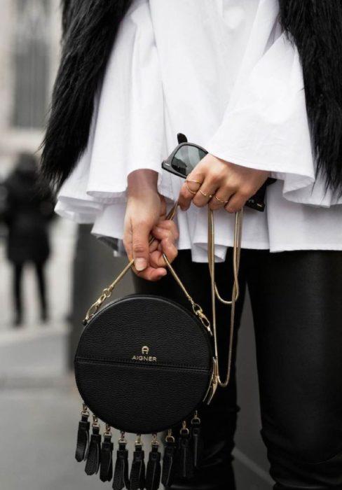 Bolso de mano pequeño color negro en forma circular y correa dorada