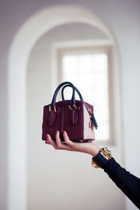 Small wine color handbag with black colored briefcases