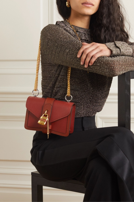 Small brick color handbag with gold details and padlock and key