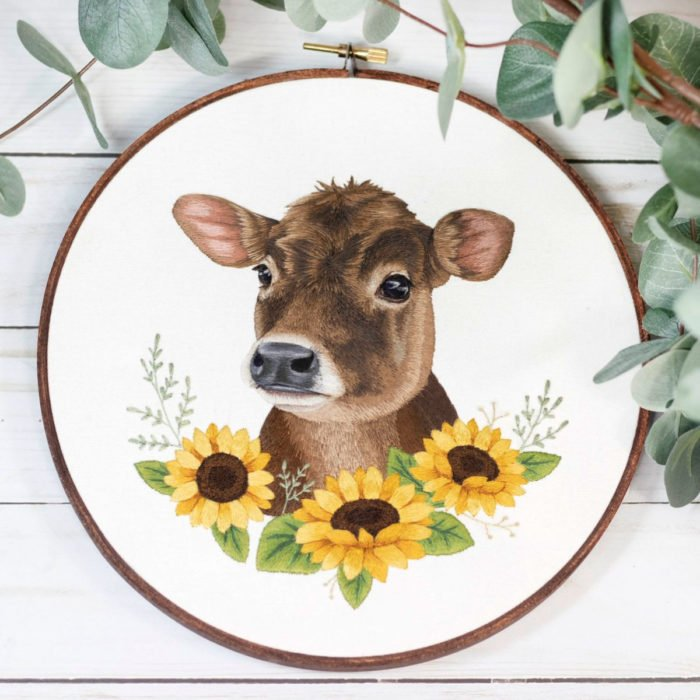 Artista Michelle Staub hace bordados de mascotas; bordado de vaca café con manchas blancas y girasoles