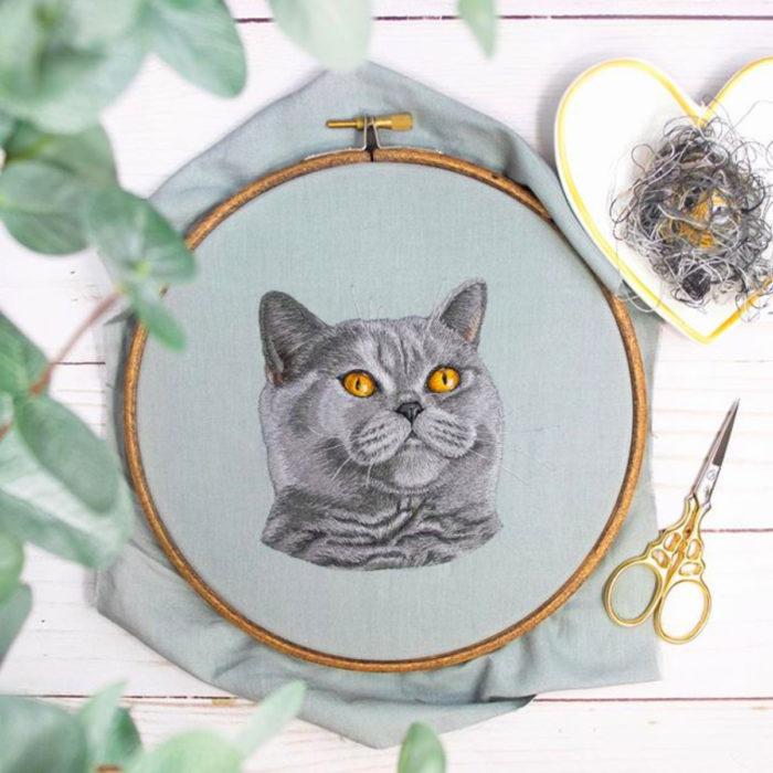 Artista Michelle Staub hace bordados de mascotas; bordado de gato gris con ojos amarillos