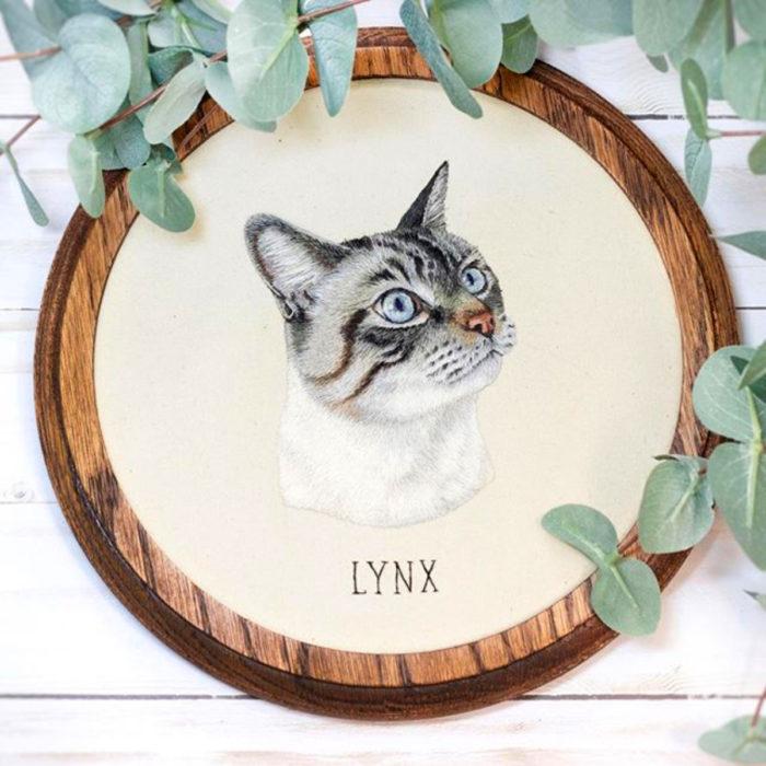 Artista Michelle Staub hace bordados de mascotas; bordado de gato blanco con rayas grises y negras, con ojos azules
