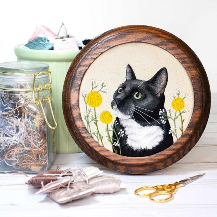 Artista Michelle Staub hace bordados de mascotas; bordado de gato negro con manchas blancas, ojos verdes y flores amarillas