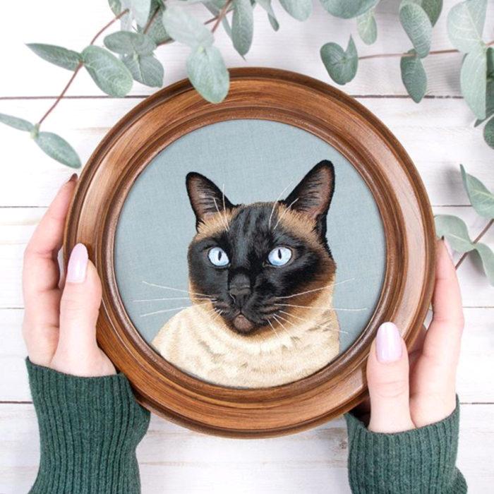 Artista Michelle Staub hace bordados de mascotas; bordado de gato siamés blanco con manchas café y negras, ojos azules
