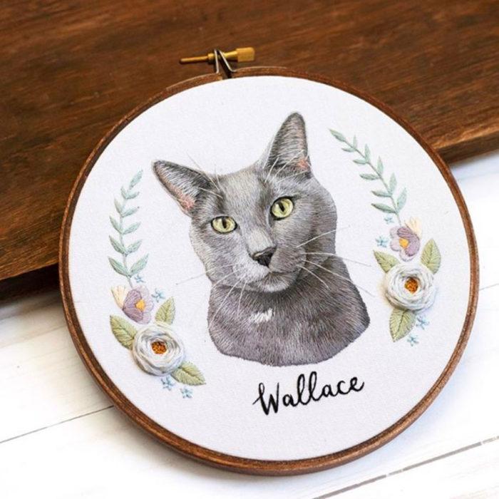 Artista Michelle Staub hace bordados de mascotas; bordado de gato gris con manchas blancas, nariz negra y ojos verdes, con flores