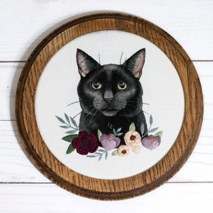 Artista Michelle Staub hace bordados de mascotas; bordado de gato negro con ojos verdes, flores rojas, moradas y blancas