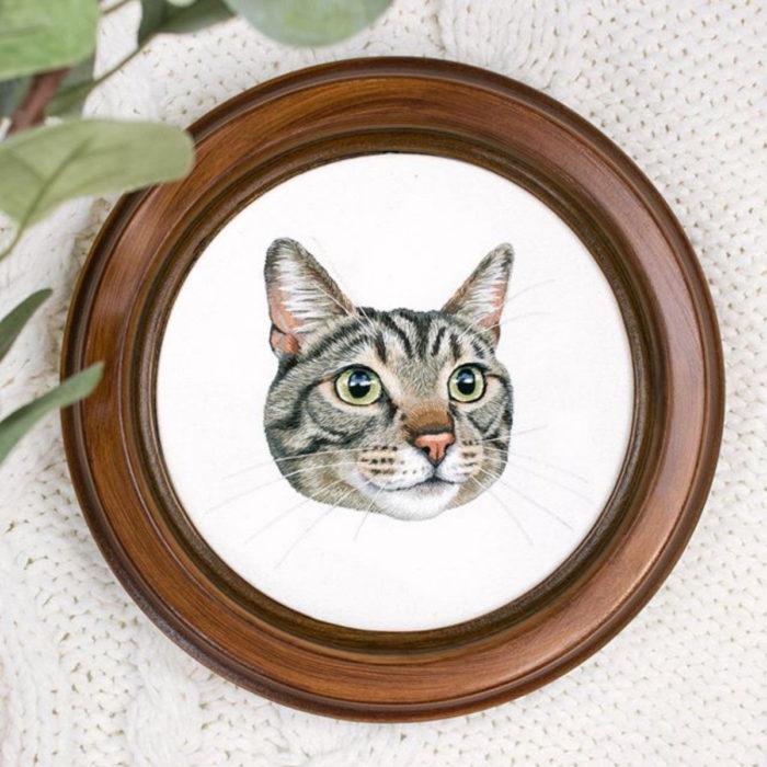 Artista Michelle Staub hace bordados de mascotas; bordado de gato gris con rayas oscuras, ojos verdes