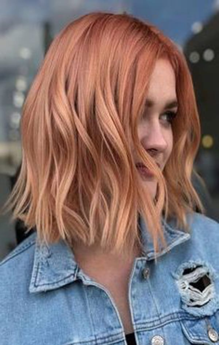Girl showing cu hair dyed in peachy copper