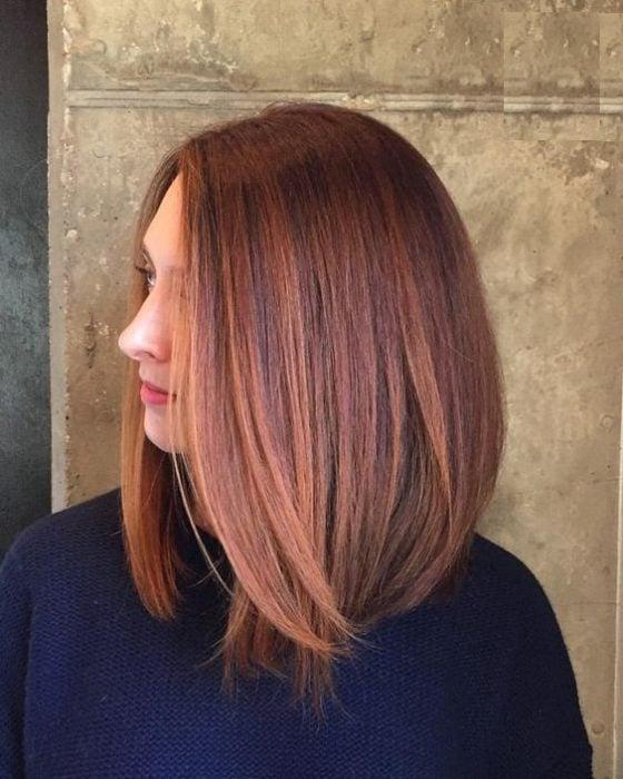 Chica con melena midi mostrando su cabello castaño deocrado con mechones peachy copper