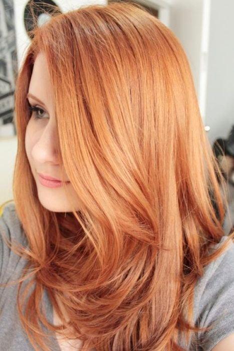 Mujer d eperfil mstrando su cabello peachy copper