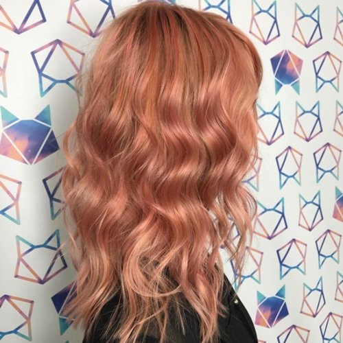Woman's hair styled in waves and dyed in peachy copper